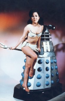 "Jill Curzon and a Dalek in a promotional photo for ""Daleks - Invasion Earth: 2150 A.D."""